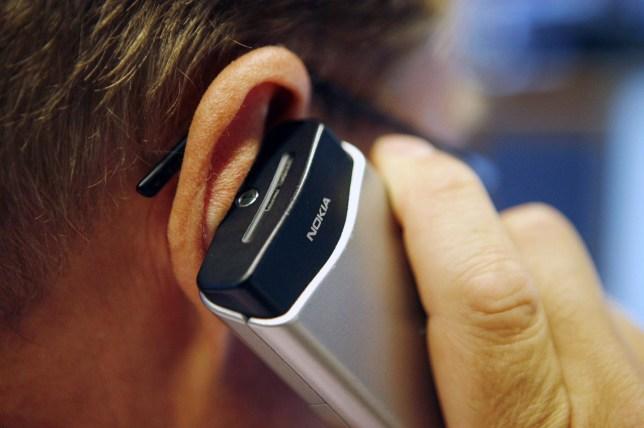 Dealer speaks on mobile phone in Nordea Bank Finland dealing room in Vallila Helsinki