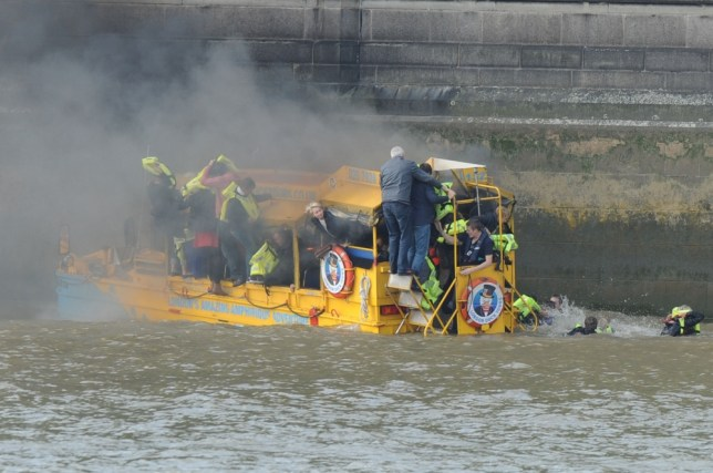 Passengers wear lifejackets on the packed boat as it billows with smoke. Some of the passengers decided to jump off the vessel and into the freezing waters of the Thames (Picture: Tony Margiocchi/Barcroft)