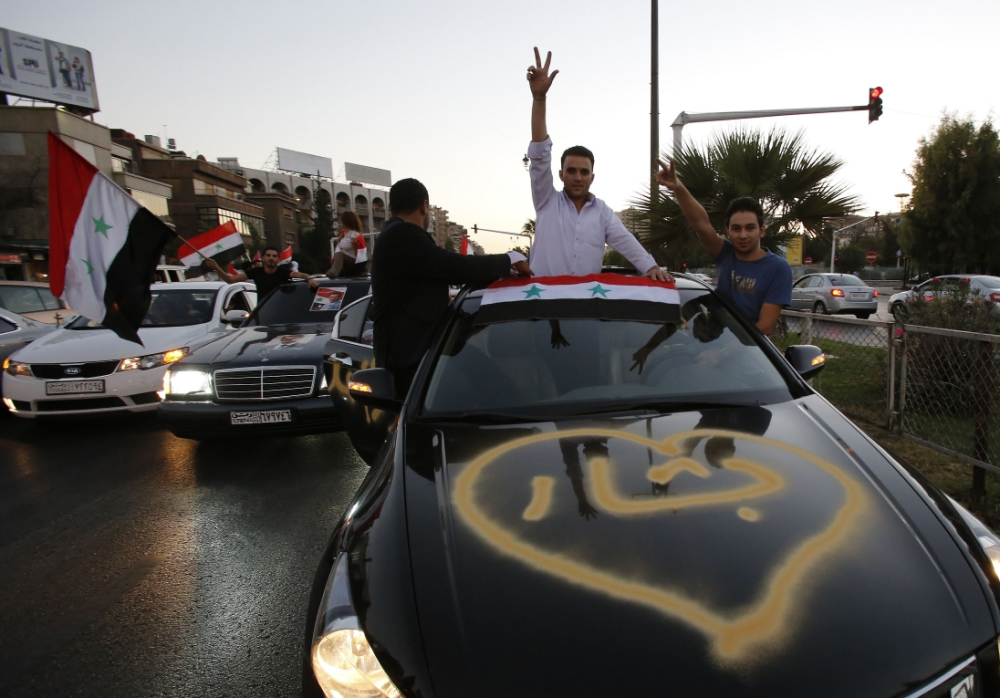 """Syrian pro-regime supporters wave their national flag and flash the sign for victory as they parade their cars in Damascus to celebrate President Bashar al-Assad's 48th birthday on September 11, 2013. The Syrian President marks his birthday as the threat of US-led strikes against his regime in response to an alleged chemical weapons attack appears to have waned while a Russian proposal that Syria hand over its chemical weapons is discussed. The text on the car reads in Arabic: """"Bashar"""". AFP PHOTO / ANWAR AMROANWAR AMRO/AFP/Getty Images"""