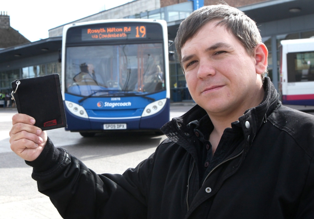 """Arthur Adlam, 31, at  Dunfermline bus station with his wallet. See swns story SWWALLET. Disabled Scot Arthur Adlam spoke of his disgust yesterday (Thur) after greedy bus bosses charged him almost £30 to return his lost wallet. Father-of-four Arthur, 31, left a wallet containing around £225, including his disability allowance, on the seat of a Stagecoach bus in his home town of Dunfermline, Fife. And when he went to the bus station to reclaim his loss, he was told it was company policy to take a 12 per cent cut plus a 50p """"admin fee"""" - a total of £27.50. Angry Adam said yesterday (Thur):  """"It's an outrage. They told me they couldn't give it back without charging me. """"They charged me for something that doesn't belong to them. No one should pay to get their own money back."""" He negotiated the fee down to £10 - but now red-faced coach chiefs have offered to give it back and review their penny-pinching policy. To add injury to insult, he became so stressed during the incident that he suffered an epileptic fit as he tried to barter with the firm."""