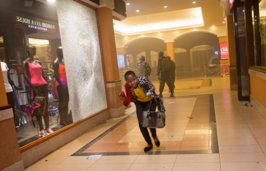 FILE - In this Saturday, Sept. 21, 2013, file photo, a woman who had been hiding during the gun battle runs for cover after armed police enter the Westgate Mall in Nairobi, Kenya, after gunmen threw grenades and opened fire Saturday, killing at least 22 people in an attack targeting non-Muslims at the upscale mall. First-hand accounts of the chaotic first hours of the four-day siege of Kenya's posh Westgate Mall are beginning to emerge. (AP Photo/Jonathan Kalan, File)
