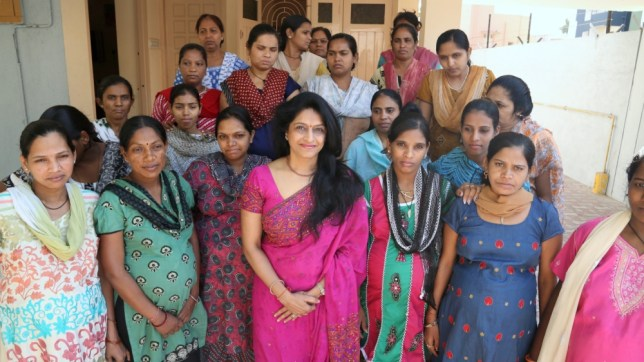 Dr Nayna Patel (front, centre, pink sari) with her heavily pregnant surrogate mothers, outside the Surrogate House. See SWNS story SWBABY: A controversial doctor is building the world's first 'baby factory' which will house hundreds of poor Indian women making babies for childless Western couples. The one-stop surrogacy shop - complete with a gift shop and hotel rooms - is under construction as part of India's growing multi billion dollar baby production industry. The medic behind the plans, Dr Nayna Patel, already runs a backstreet clinic in a town in Gujarat, which currently accommodates around 100 pregnant women in a single house. Wannabe parents send sperm to the clinic via courier, only visiting India to pick up their new son or daughter. Hopeful parents are charged $28,000 - with $8,000 given to the poor Indian surrogate mother when she hands over the child.