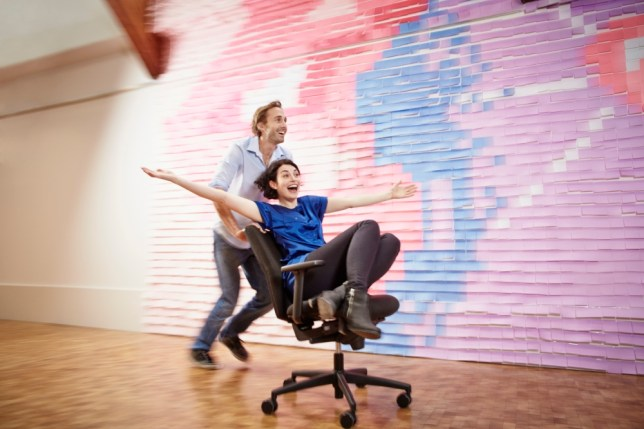Man pushing woman on office chair at wall with sticky notes --- Image by   Oliver Rossi/Corbis