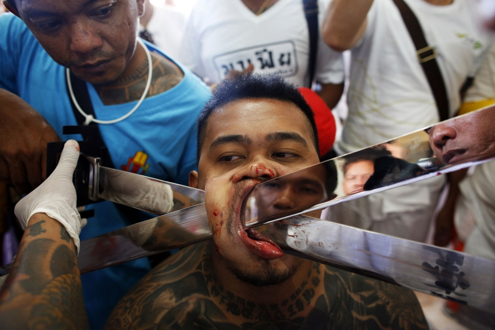 ATTENTION EDITORS - GRAPHIC CONTENT     A devotee of the Chinese Bang Neow Shrine has another blade pierced through his cheek before the beginning of a street procession during the annual vegetarian festival in Phuket October 10, 2013. The festival, featuring face-piercing, spirit mediums and strict vegetarianism celebrates the local Chinese community's belief that abstinence from meat and various stimulants during the ninth lunar month of the Chinese calendar will help them obtain good health and peace of mind. REUTERS/Athit Perawongmetha (THAILAND - Tags: RELIGION SOCIETY) TEMPLATE OUT