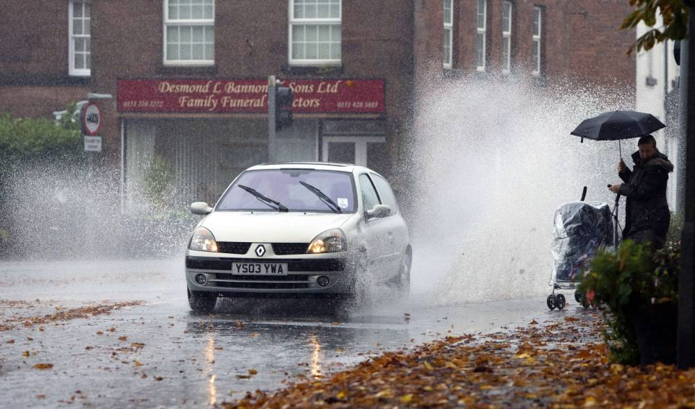 A lady with a child in a pram gets an unwelcomed soaking from a passing car in Gateacre, Liverpool after heavy rain fell over the country. PRESS ASSOCIATION Photo. Picture date: Monday October 28, 2013. Photo credit should read: Peter Byrne/PA Wire