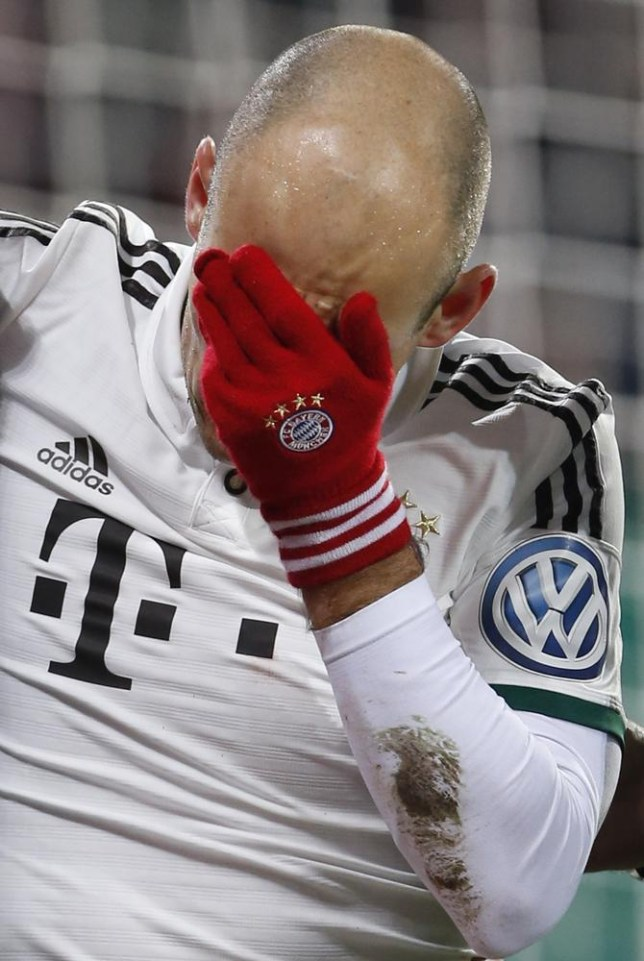 Bayern's Arjen Robben of the Netherlands covers his face after a collision with goalkeeper Marwin Hitz of Switzerland during the German soccer cup third round match between FC Augsburg and FC Bayern Munich in Augsburg, southern Germany, Wednesday, Dec. 4, 2013. (AP Photo/Matthias Schrader) AP Photo/Matthias Schrader