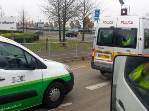 A bad call: Dozy driver on phone behind the wheel busted by van of police officers