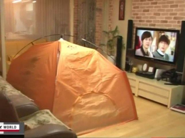 A South Korean family snuggle up in their tent to watch TV. Inside, the temperature is 26C (79F), compared with 18C (64F) in their unheated living room (Picture: NHK World)