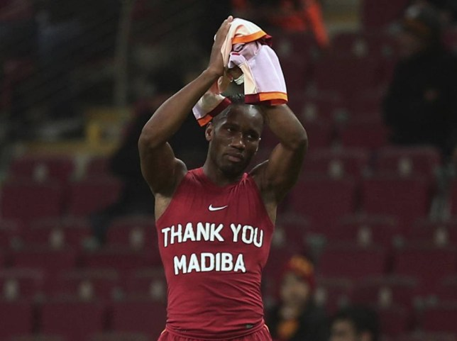 Galatasaray's Didier Drogba from Ivory Coast salutes soccer fans as he wears a jersey in sign of respect for Nelson Mandela before their Turkish League match with Elazigspor in Istanbul, Turkey, Friday, Dec. 6, 2013. South Africa is readying itself for the arrival of a flood of world leaders for the memorial service and funeral of Nelson Mandela as thousands of mourners continued to flock to sites around the country Saturday to pay homage to the freedom struggle icon, who died Thursday in Johannesburg at the age of 95.(AP Photo)