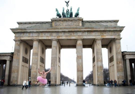 Bob Carey, dressed in a pink tutu, jumps in front of the Brandenburg Gate in Berlin, Germany, for The Tutu Project, to help women with breast cancer