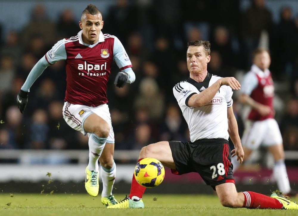 West Ham United's Ravel Morrison, left, controls the ball past Fulham's Scott Parker during their English Premier League soccer match in London, Saturday, Nov. 30, 2013. West Ham United won the match 3-0. (AP Photo/Lefteris Pitarakis) AP Photo/Lefteris Pitarakis