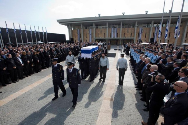 The coffin of late Israeli Prime Minister Ariel Sharon is carried after a memorial ceremony outside the Knesset, in Jerusalem, Monday, Jan. 13, 2014. Israel is holding a state memorial ceremony for Sharon at the country's parliament building. Monday's official ceremony in the Knesset in Jerusalem will be followed by a private burial on the family's desert ranch in southern Israel. (AP Photo/Sebastian Scheiner)