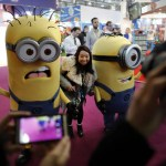 CAPTION CORRECTION: ADDING EVENT A visitor poses for a photograph with people dressed as giant Minions characters during a photocall for the annual Toy Fair at the Olympia exhibition centre in London, on January 21, 2014. Toy Fair, the only dedicated toy, game and hobby exhibition in Britain, features over 280 companies competing for business. AFP PHOTO / ADRIAN DENNISADRIAN DENNIS/AFP/Getty Images