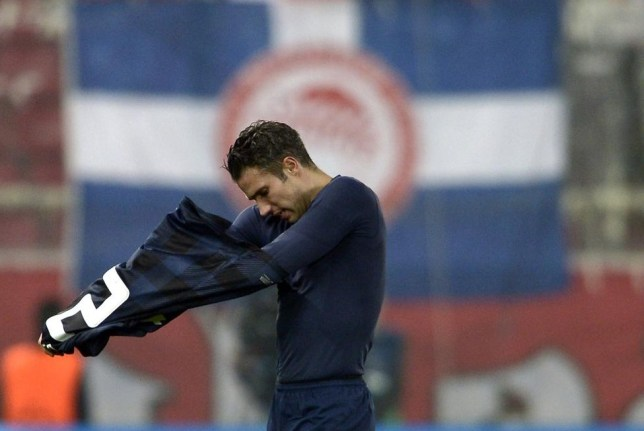 Manchester United's Dutch forward Robin van Persie takes off his jersey after losing the round of 16 Champions League football match Olympiakos vs Manchester United at Karaiskaki Stadium in Athens on February 25, 2014. AFP PHOTO / ARIS MESSINIS ARIS MESSINIS/AFP/Getty Images