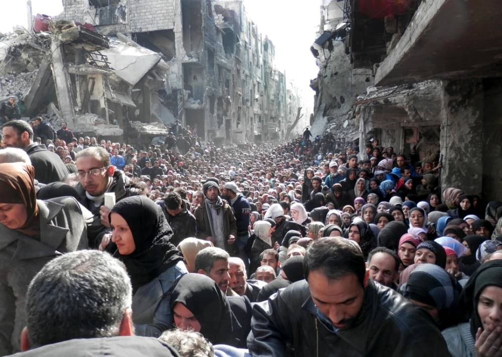 'Sea of ghosts' as refugees queue for food in Syria