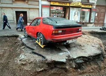 A Porsche trapped in the road as diggers leave it behind