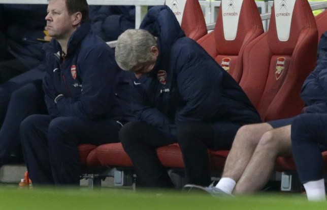 Arsenal's French manager Arsene Wenger, center, looks down during the English Premier League soccer match between Arsenal and Swansea City at the Emirates Stadium in London, Tuesday, March 25, 2014. (AP Photo/Matt Dunham) AP Photo/Matt Dunham