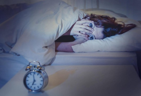 woman with red hair in her bed with insomnia and can't sleep waiting for her alarm clock to go off on a white background OcusFocus/OcusFocus