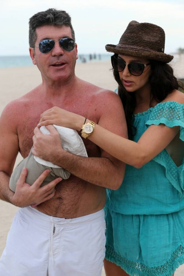Simon Cowell carries his son Eric in from the beach while girlfriend Lauren Silverman carefully looks on