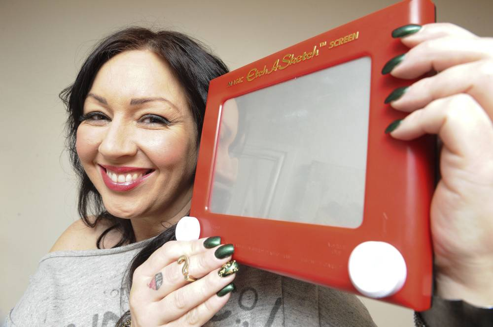 PIC BY DAN ROWLANDS / CATERS NEWS (PICTURED: SARAH BEAL WITH AN ETCH A SKETCH) - A mother of two with a rare skin condition can DRAW on her own skin and watch it disappear - just like an ETCH A SKETCH. Sarah Beal, 43, from Arley, Warwickshire, has such sensitive skin that the slightest scratch can cause it to swell. But remarkably, Sarah has realised that the condition - known as dermatographia - allows her to create patterns and pictures on her skin which disappear within an hour. Sarah said: My skin is so sensitive that sometimes even clothes can feel uncomfortable.