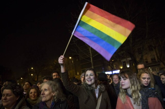 LONDON, ENGLAND - MARCH 29: A woman waves a rainbow flag as gay couple Peter McGraith and David Cabreza leave Islington Town Hall  where they were married shortly after midnight at in one of the UK's first same-sex weddings on March 29, 2014 in London, England. Same sex couples have been able to enter into 'civil partnerships' since 2005, however following a change in the law in July 2013 gay couples are now eligible to marry in England and Wales. A number of gay couples have arranged for their wedding ceremonies to take place shortly after midnight on March 29, 2014 to become some of the first to take advantage of the new law. Parliament's decision to grant same sex couples an equal right to marriage has been met with opposition from religious groups. Gay marriage is currently being debated in Scotland, however the Northern Ireland administration has no plans to make it law.(Photo by Rob Stothard/Getty Images)