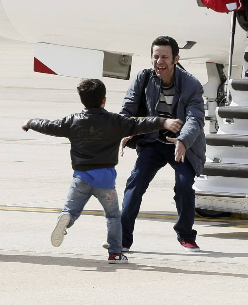 El Mundo correspondent Javier Espinosa is greeted by his son as he arrives at the military airbase in Torrejon de Ardoz, near Madrid