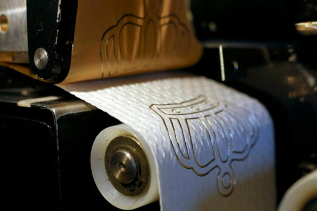 Luxury toilet paper with a 24 carat gold motifs is produced at the Tissue Design workshop of Fritz Loibl in Grafenau March 31, 2014.  Each gold embossed toilet roll, which is handcrafted by owner Fritz Loibl with customised designs, costs 179 Euros (246 $) and are sold worldwide.  REUTERS/Michael Dalder (GERMANY - Tags: SOCIETY)
