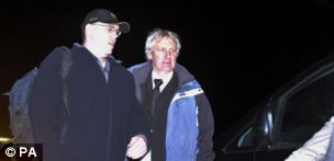 Freed hostage Peter Moore (left, with cap) gets into a waiting car after arriving at RAF Brize Norton in Oxfordshire