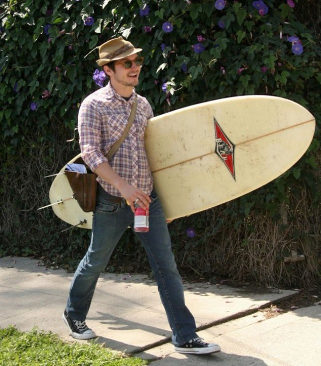 Elijah Wood clutches on to his surf board