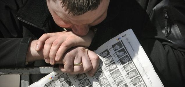 A man holds a newspaper showing the victims of the crashed Polish presidential plane while waiting for the arrival of Lech Kaczynski's coffin