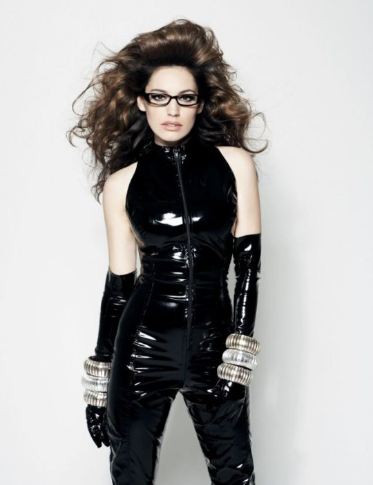 Kelly Brook wears glasses and a sexy black PVC jumpsuit