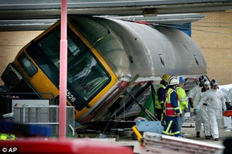 Members of the emergency services are seen removing a body from the scene of the Potters Bar rail crash
