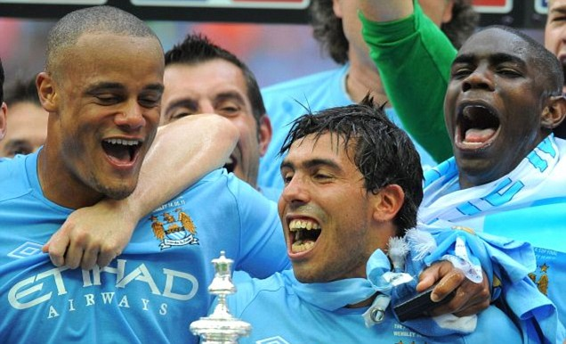 Carlos Tevez celebrates with his Manchester City team-mates after their FA Cup victory