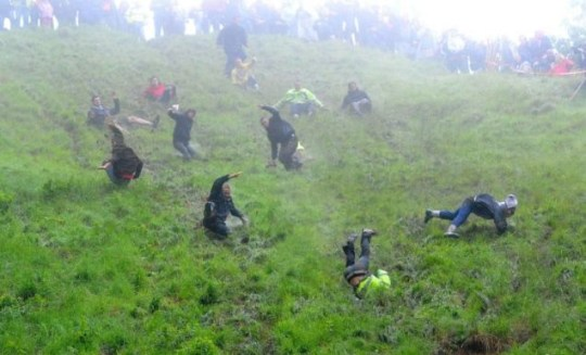 Going downhill rapidly: competitors take part in the cheese-rolling on Coopers Hill, Gloucestershire (PA)