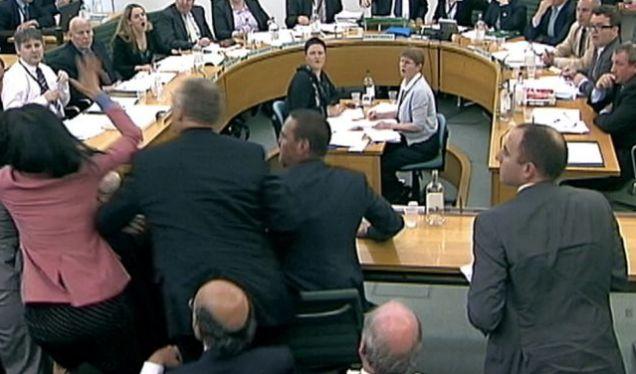 Wendi Deng (in pink) strikes back after her husband Rupert Murdoch was hit with a foam pie (Reuters)