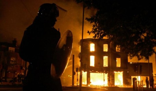 A police officer stands near a burning furniture store on Reeves Corner in Croydon on Monday night (PA)