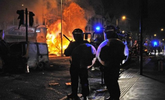 Riot policemen in front of a burning building in Croydon on Monday night: police have warned Facebook users against attempting to incite any further violence (Picture: AFP/Getty)