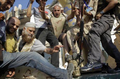 Rebel fighters stomp on the head of a Gaddafi statue inside his compound in Bab al-Aziziya in Tripoli, Libya