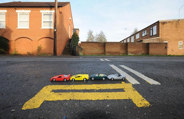 Model cars are lined up on what is believed to be Britain's shortest set of double yellow lines - measuring just 17in