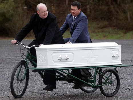 Rev. Paul Sinclair with his tandem hearse and Steve Soult who designed the coffin is pedaling behind