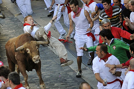 One of the 'runners' gets hit by a rampaging Pamplona bull
