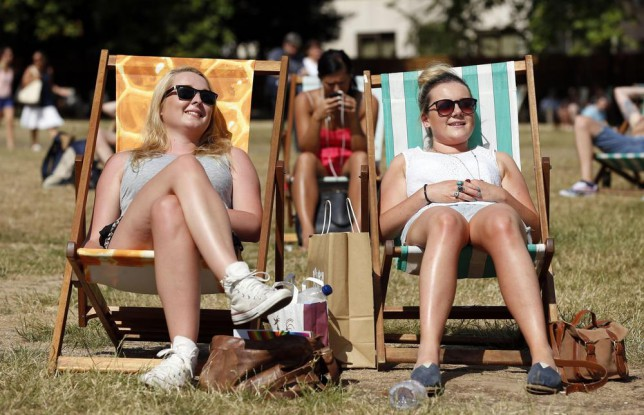 File photo dated 15/07/13 of women sunbathing in Green Park, central London, Britain is in the midst of its first heatwave for seven years, and there is no sign of the mercury plummeting any time soon. Jonathan Brady/PA Wire/Press Association Images