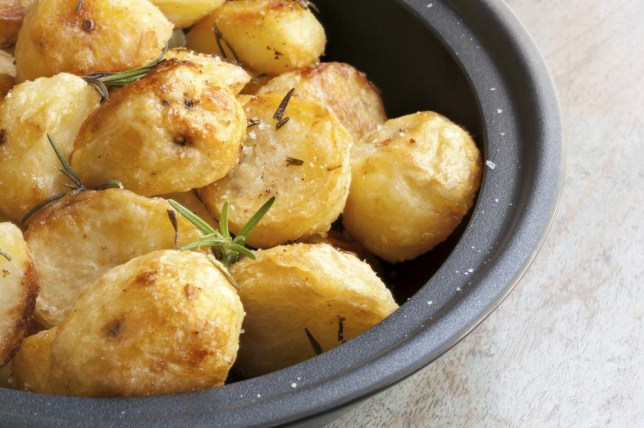 Roasted potatoes in black dish, with rosemary and sea salt flakes. Timber background.Roasted potatoes in black dish, with rosemary and sea salt flakes. Timber background. robynmac/robynmac