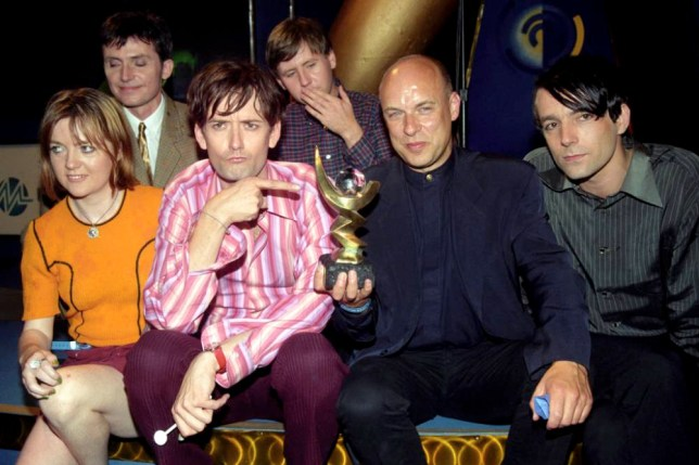 Pulp frontman Jarvis Cocker points at the 1996 Mercury Music Prize, awarded for their album 'Different Class'at tonight's (Tuesday) London ceremony. They donated the  25,000 cheque and award to WarChild Help producer Brian Eno (2nd right). See PA story SHOWBIZ Pulp. Photo by Stefan Rousseau/PA
