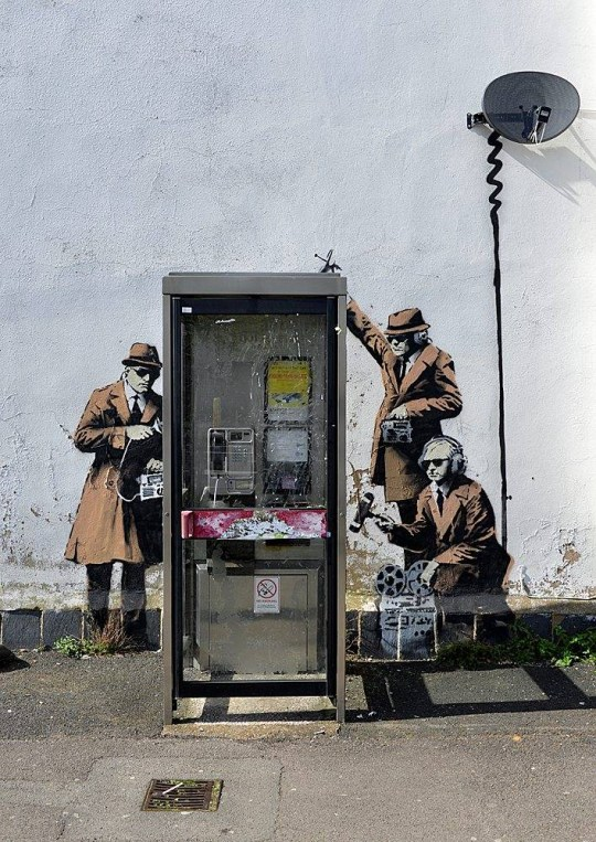 The new Banksy which has appeared in Cheltenham, the home of government surveillance agency GCHQ. See SWNS story SWBANKSY; It looks as though celebrated street artist Banksy may have been in Cheltenham. Images of wall art resembling the Bristol artistís style have appeared on the side of a house on the corner of Fairview Road and Hewlett Road overnight. They depict 1950s-style spies, clad in trench coat and trilby hats, carrying listening devices. They provide a perfect foil to Cheltenhamís role as the home for listening post, GCHQ. The painted figures, on a wall surrounding a BT telephone box appeared overnight on Sunday morning.