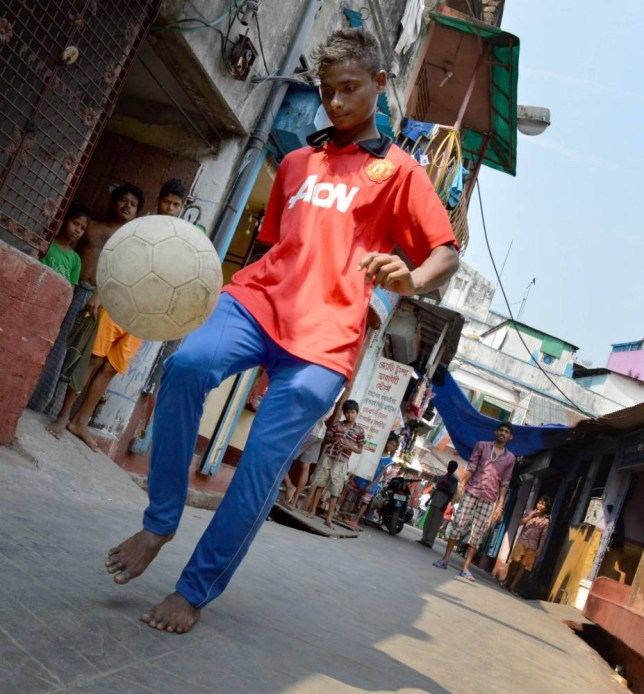 Rajib Roy, 16, plays football in the Kolkata slum where he grew up. In a few days time the football mad son of a penniless sex worker will fly to Manchester to train for the Red Devils. See SWNS story SWSLUM;  A 16 year-old is on the brink of one of the biggest rags-to-riches stories ever - from the back streets of Kolkata to the front stage of Manchester United. Rajib Roy, the son of a dirt-poor sex worker, could become a real-life Slumdog Millionaire after being chosen to train at Old Trafford. The talented teenager caught the eye of United scouts at a national tournament for India's best youngsters. He is one of 11 youngsters from India who have been given the chance of a lifetime - spending 15 days training with United's under-21 squad.