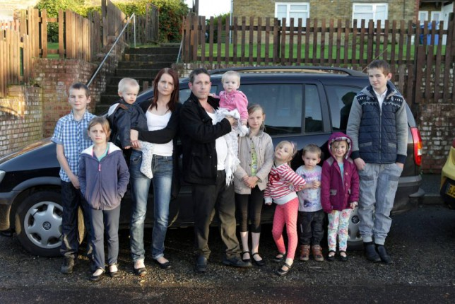 Cheryl Prudham her husband Robert and their nine children at their home in Sittingbourne, Kent. See MASONS story MNTWINS; The couple, who live on benefits, have announced they are pregnant again with twins. According to the Sun the couple receive £38,000 a year in state handouts and recently did a house swap to move to a 5 bedroom council house.