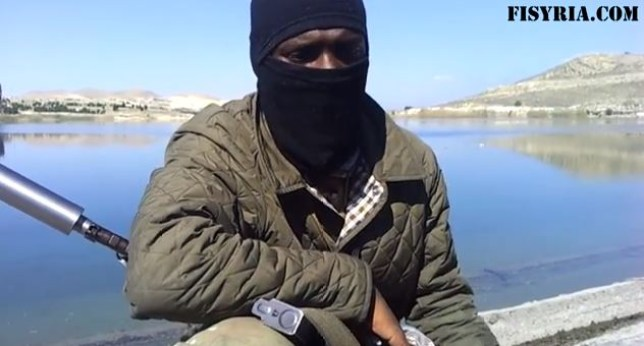 The man was filmed wearing a mask and holding a gun (Picture: FISyria.com)