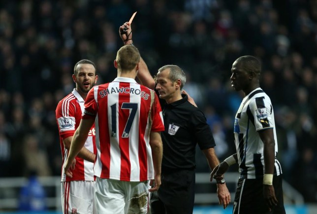 Stoke City's Northern Irish-born Irish defender Marc Wilson (L) is shown a red card by referee Martin Atkinson during the English Premier League football match between Newcastle United and Stoke City at at St James' Park in Newcastle-upon-Tyne, northeast England on December 26, 2013. Newcastle won the game 5-1. AFP PHOTO / IAN MACNICOL RESTRICTED TO EDITORIAL USE. No use with unauthorized audio, video, data, fixture lists, club/league logos or live services. Online in-match use limited to 45 images, no video emulation. No use in betting, games or single club/league/player publications. IAN MACNICOL/AFP/Getty Images
