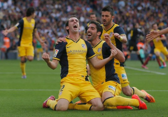 Atletico's Diego Godin from Uruguay, left, celebrates with teammates after scoring his side's first goal during a Spanish La Liga soccer match between FC Barcelona and Atletico Madrid at the Camp Nou stadium in Barcelona, Spain, Saturday, May 17, 2014. (AP Photo/Andres Kudacki)